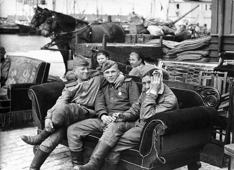 Soviet soldiers sit on a sofa in the open air on the dock of the Danish town
