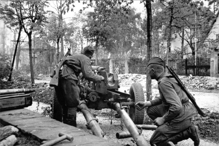Soviet soldiers fire artillery at pockets of German resistance as they enter the suburbs of Berlin.