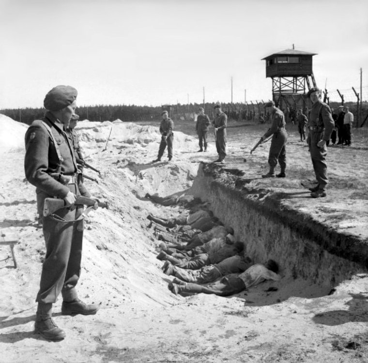 British soldiers permit former SS camp guards at Bergen-Belsen concentration camp to rest.