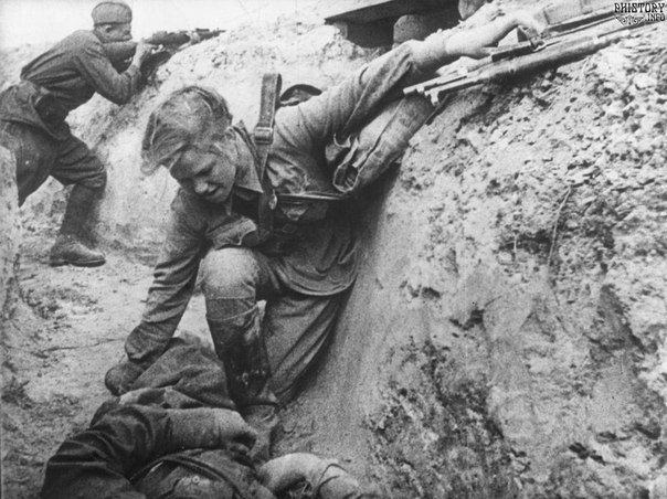 Soviet nurse assisting a fallen comrade in a trench